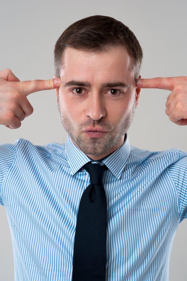 Hombre de negocios con los fingeres en cara como arma imagenes de archivo