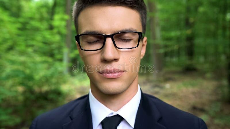Hombre de negocios con los ojos cerrados que sienten la conexión con la naturaleza, libertad, meditación foto de archivo