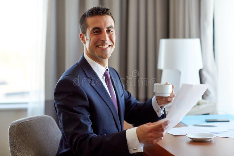 Hombre de negocios con los papeles que bebe el café en el hotel foto de archivo