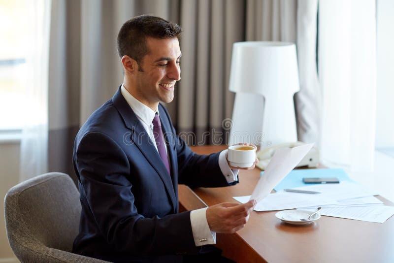 Hombre de negocios con los papeles que bebe el café en el hotel fotografía de archivo libre de regalías