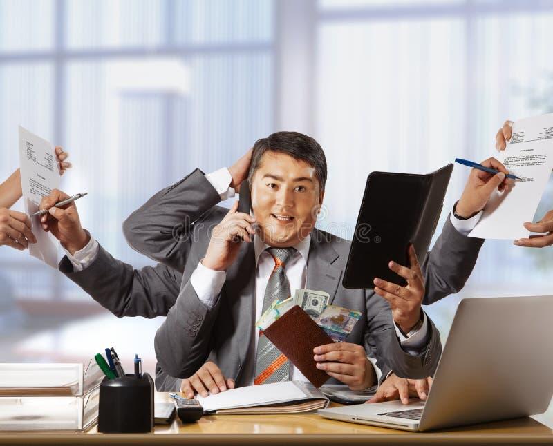 Hombre de negocios con ocho manos en notepa elegante del control del funcionamiento del traje imagen de archivo