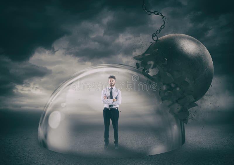 Hombre de negocios con seguridad dentro de una bóveda del escudo durante una tormenta que lo protege contra una bola arruinadora  imagen de archivo