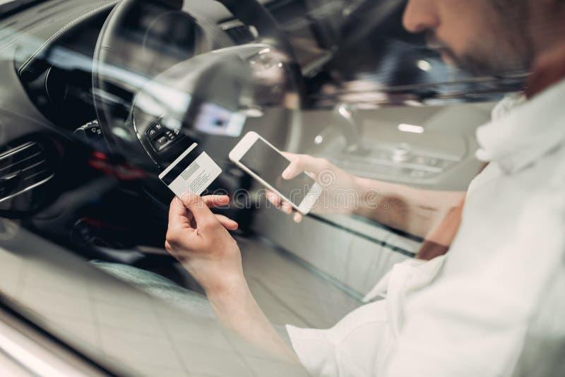 Hombre de negocios con smartphone que hace compras en línea en el coche imagenes de archivo