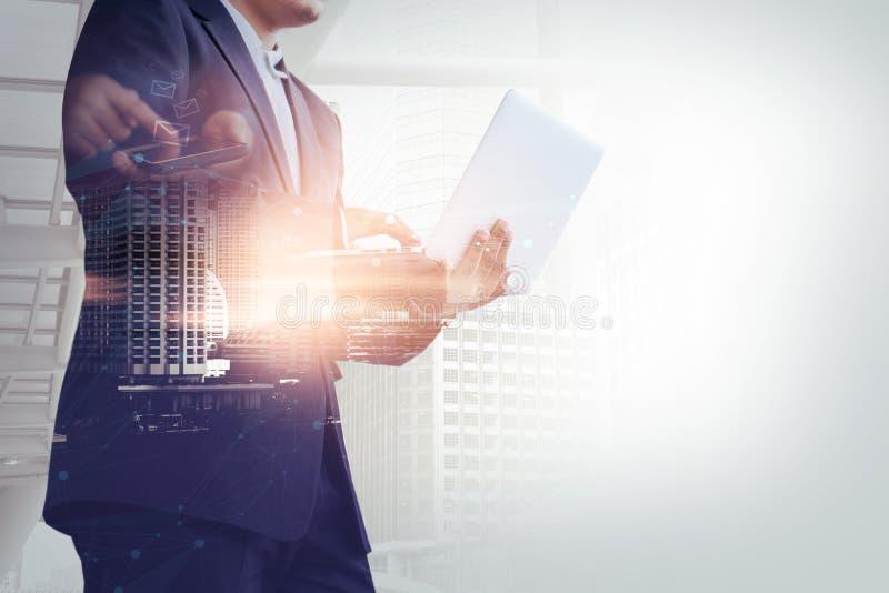 Hombre de negocios con smartphone social de la red del ai de la tecnología y ordenador portátil del ordenador con la ciudad de la foto de archivo