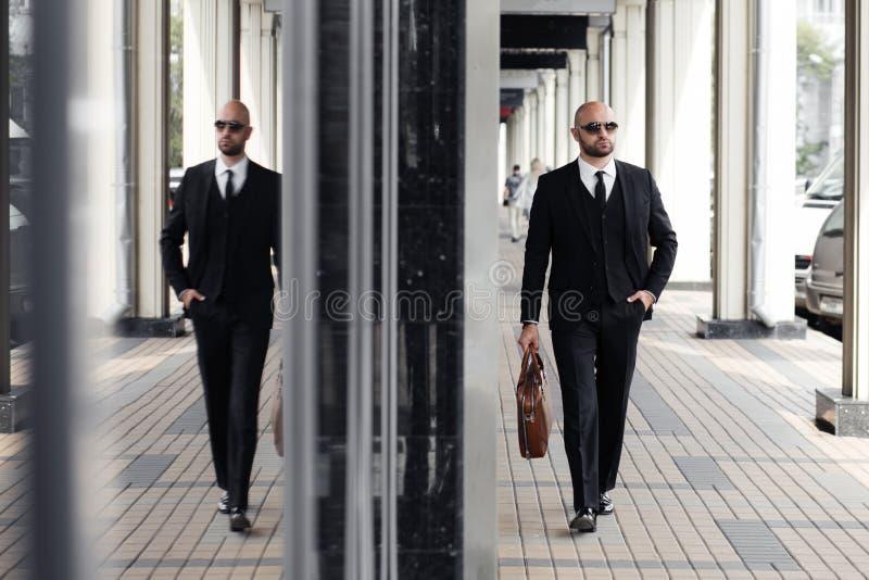 Hombre de negocios con un bolso cerca de la oficina que habla en el teléfono foto de archivo