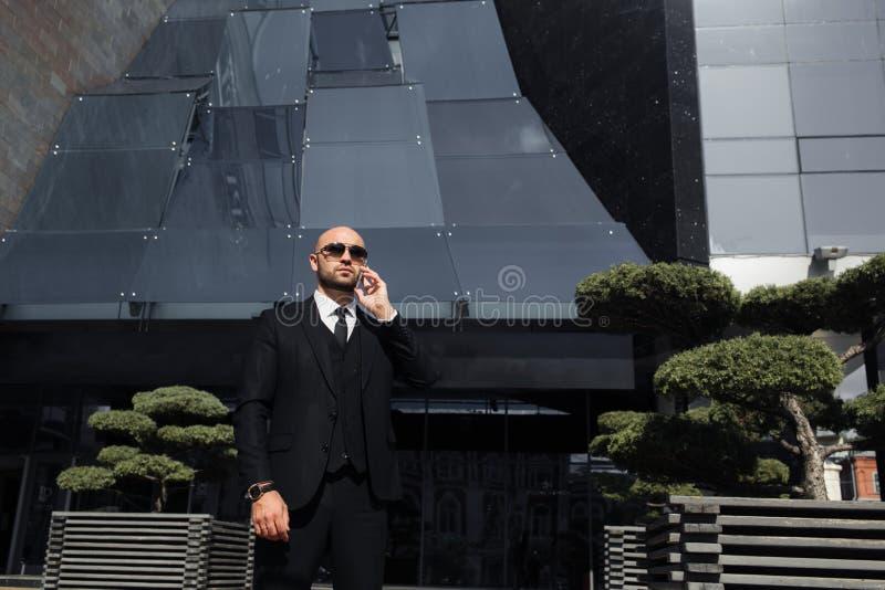 Hombre de negocios con un bolso cerca de la oficina que habla en el teléfono imagenes de archivo