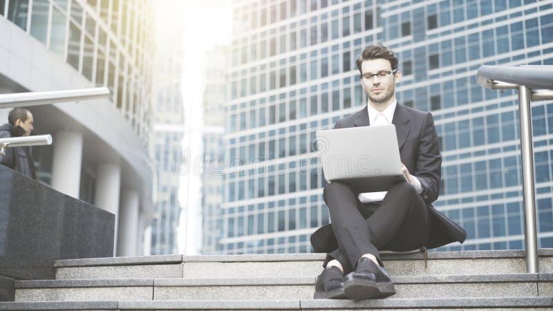 Hombre de negocios con un ordenador portátil que trabaja en el al aire libre imagen de archivo
