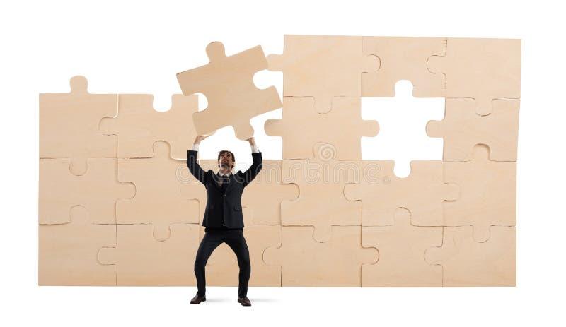 Hombre de negocios con un pedazo de rompecabezas Construya el concepto del negocio foto de archivo libre de regalías