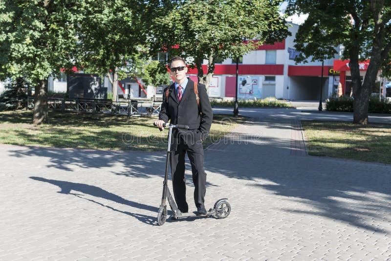 Hombre de negocios con una vespa del retroceso en parque fotografía de archivo