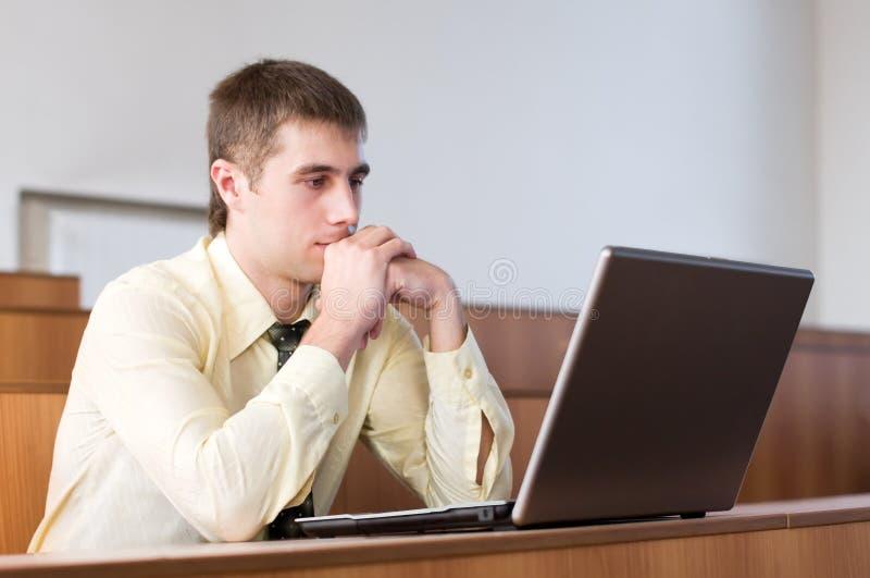 Hombre de negocios concentrado con la computadora portátil imagen de archivo