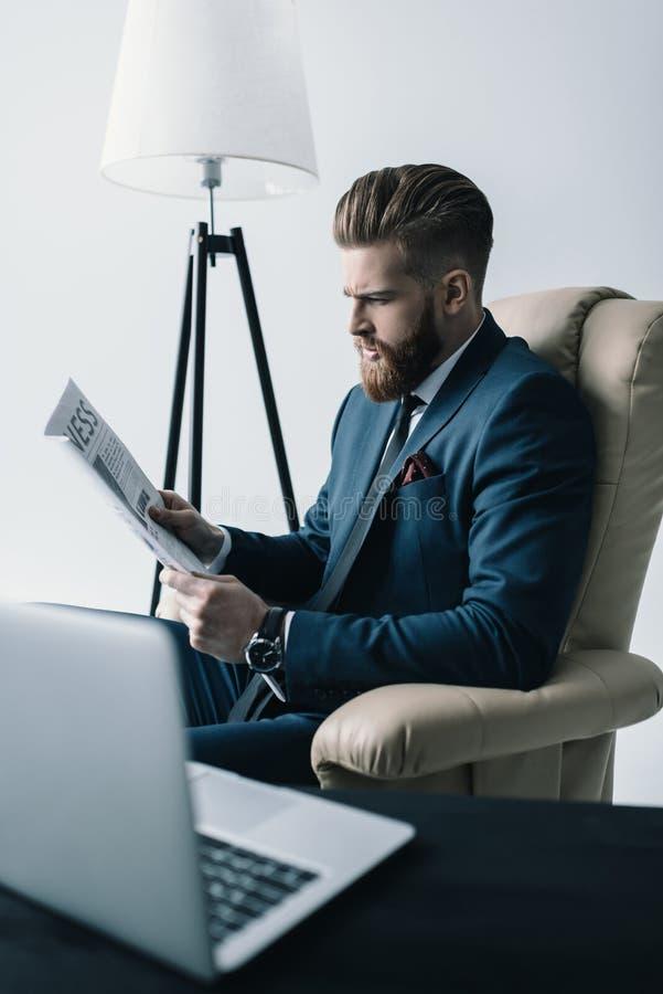 Hombre de negocios concentrado en periódico de la lectura de la butaca fotos de archivo
