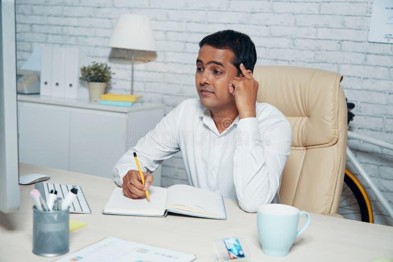 Hombre de negocios concentrado que trabaja en el escritorio fotos de archivo libres de regalías