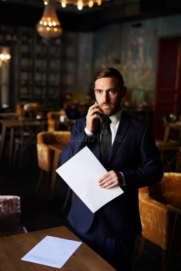 Hombre de negocios concentrado usando el teléfono móvil fotografía de archivo