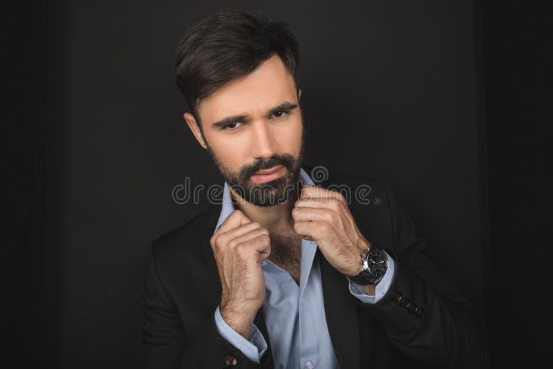 Hombre de negocios confiado barbudo hermoso que presenta en traje negro foto de archivo