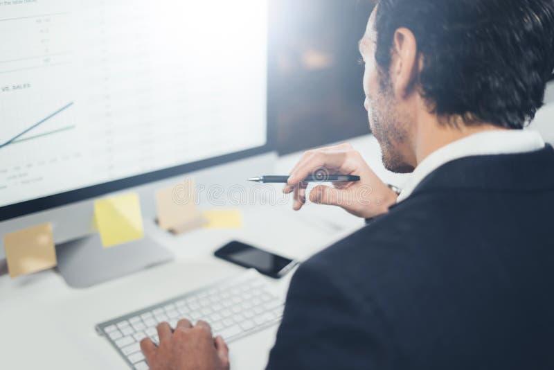 Hombre de negocios confiado en desgaste formal que piensa y que trabaja con el equipo de escritorio en la oficina lightful modern fotografía de archivo libre de regalías