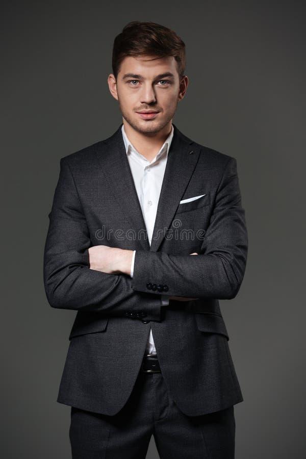 Hombre de negocios confiado hermoso en el traje negro que se coloca con los brazos cruzados imágenes de archivo libres de regalías