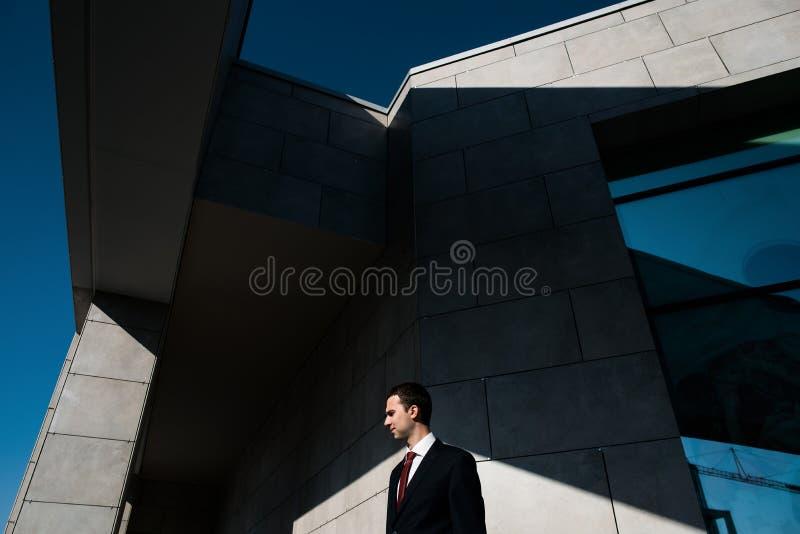 Hombre de negocios confiado hermoso en el traje que presenta en el edificio industrial moderno Foto abstracta blanco y negro con fotografía de archivo