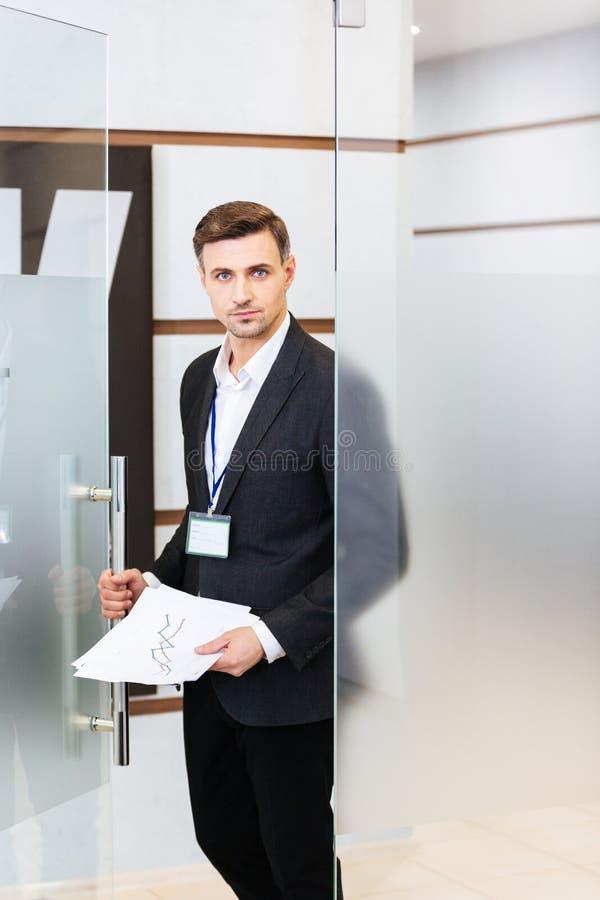 Hombre de negocios confiado hermoso que entra en la oficina imagen de archivo libre de regalías