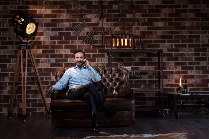 Hombre de negocios confiado independiente que se sienta en el sofá imagen de archivo