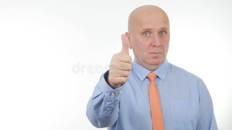Hombre de negocios confiado Make Thumbs Up una buena muestra seria del trabajo foto de archivo libre de regalías