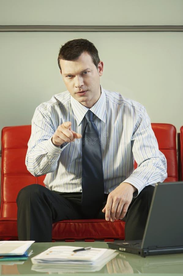 Hombre de negocios confiado Pointing While Sitting en el sofá rojo foto de archivo libre de regalías