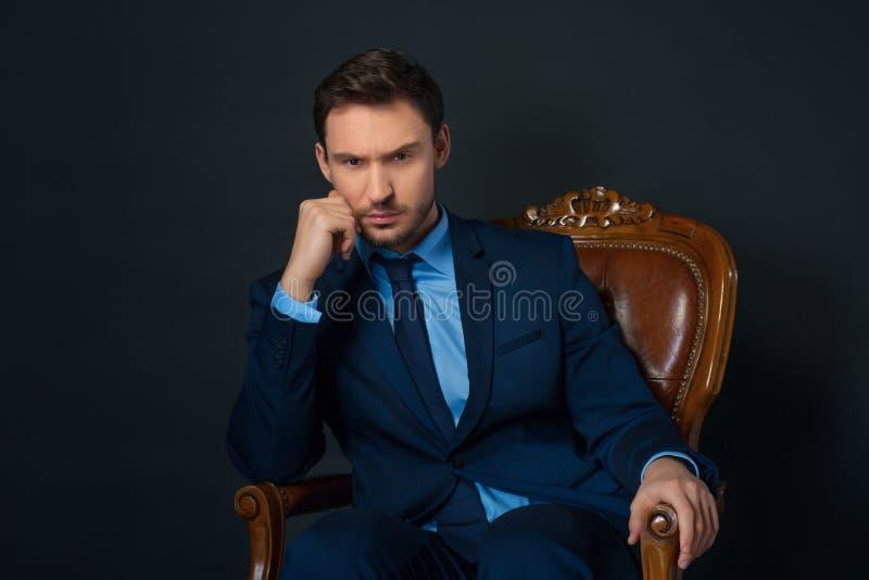 Hombre de negocios confiado que se sienta en butaca imagen de archivo libre de regalías