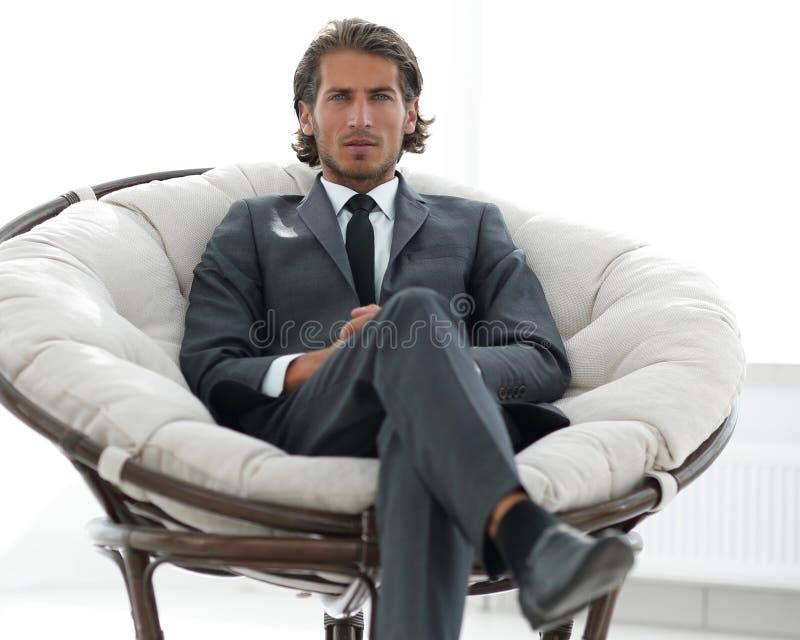 Hombre de negocios confiado que se sienta en una silla cómoda grande fotos de archivo