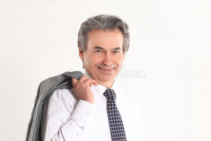 Hombre de negocios confiado que sostiene una chaqueta sobre su hombro Aislado en el fondo blanco imagen de archivo