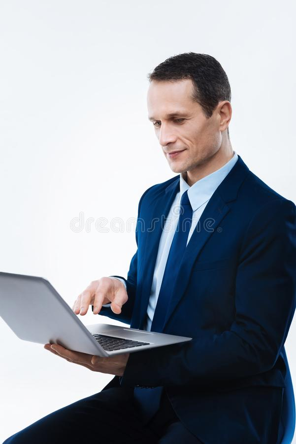 Hombre de negocios confiado serio que trabaja en el ordenador portátil imagen de archivo libre de regalías