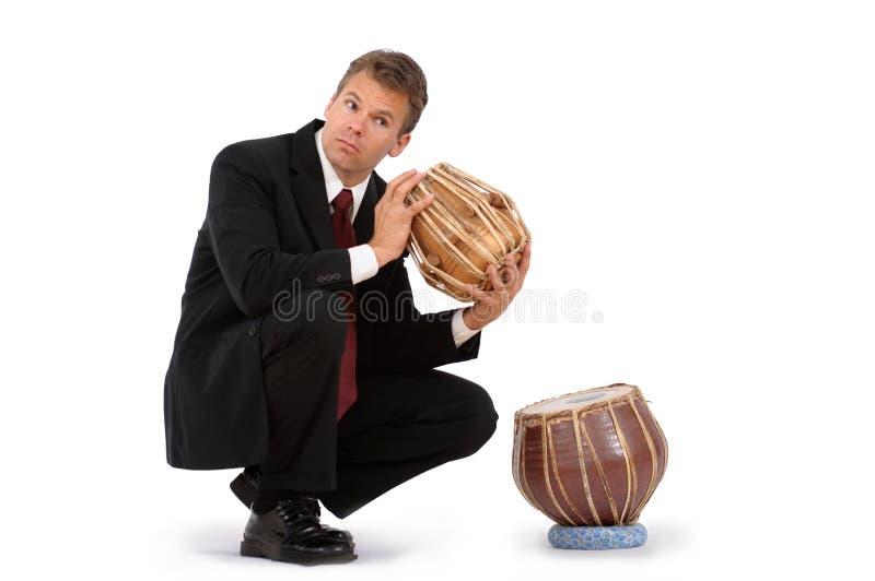 Hombre de negocios confundido sobre el tambor indio étnico imagen de archivo libre de regalías