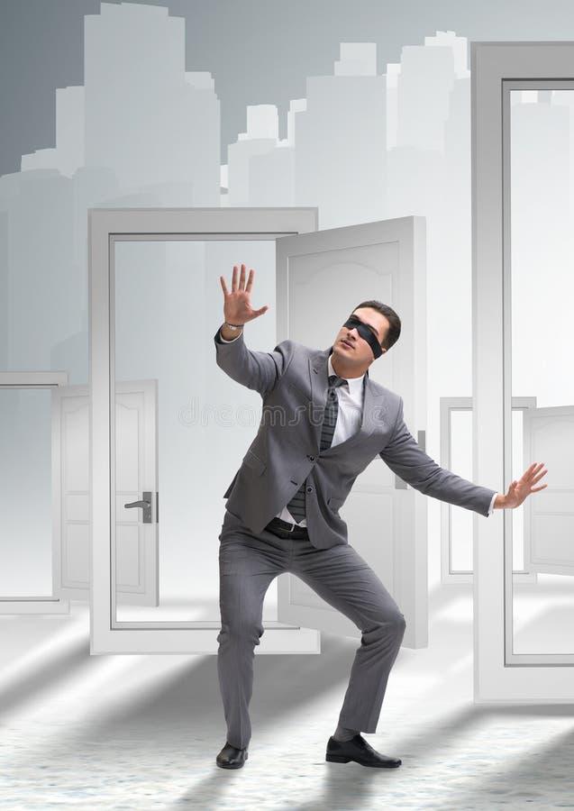Hombre de negocios confuso delante de puertas fotografía de archivo libre de regalías