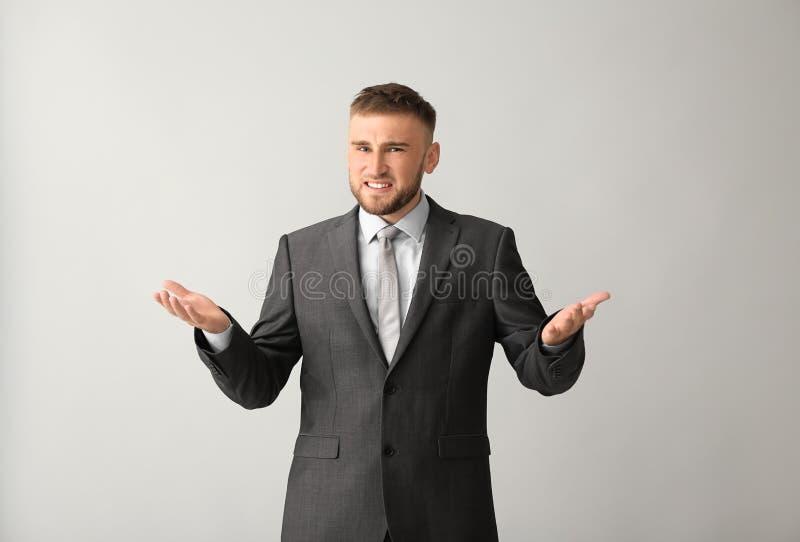 Hombre de negocios confuso en fondo gris fotos de archivo