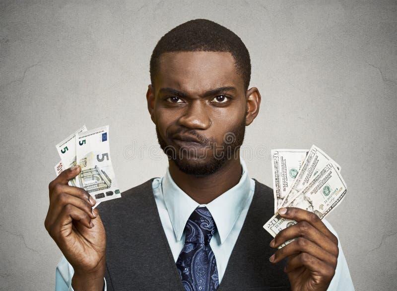 Hombre de negocios confuso que lleva a cabo el dólar, cuentas euro fotos de archivo