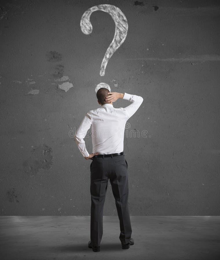 Hombre de negocios confuso que mira el signo de interrogación fotos de archivo libres de regalías