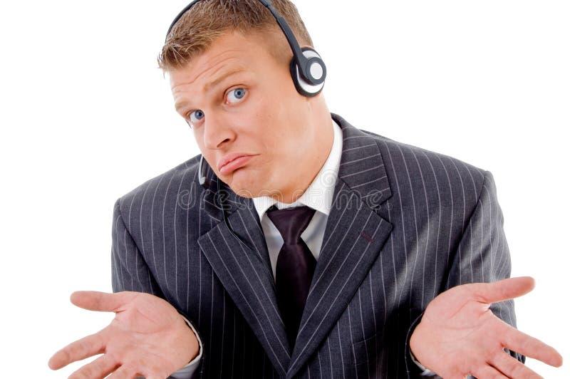 Hombre de negocios confuso que presenta con el receptor de cabeza imagenes de archivo