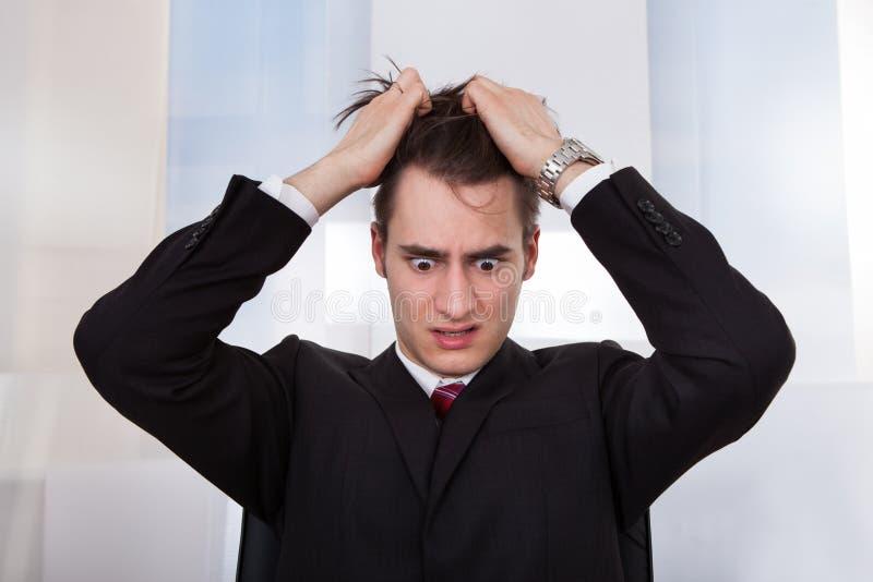 Hombre de negocios confuso que tira del pelo fotografía de archivo