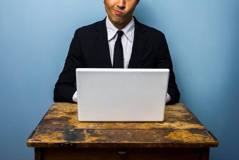 Hombre de negocios confuso que trabaja en el ordenador portátil fotos de archivo