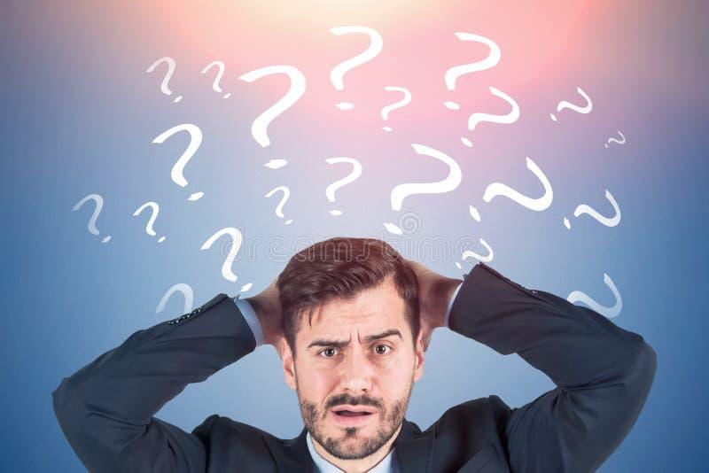 Hombre de negocios confuso, signos de interrogación azules fotos de archivo