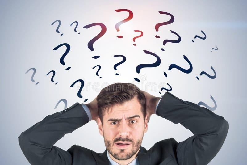 Hombre de negocios confuso, signos de interrogación grises fotografía de archivo