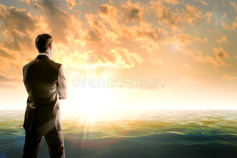 Hombre de negocios contra el mar en luz de la mañana foto de archivo libre de regalías