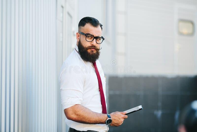 Hombre de negocios contra una pared blanca imagen de archivo