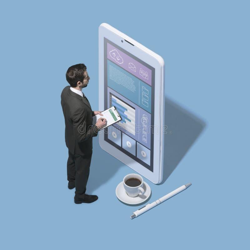 Hombre de negocios corporativo minúsculo que trabaja con los apps móviles foto de archivo