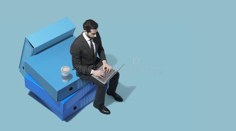 Hombre de negocios corporativo miniatura que trabaja con su ordenador portátil fotos de archivo libres de regalías