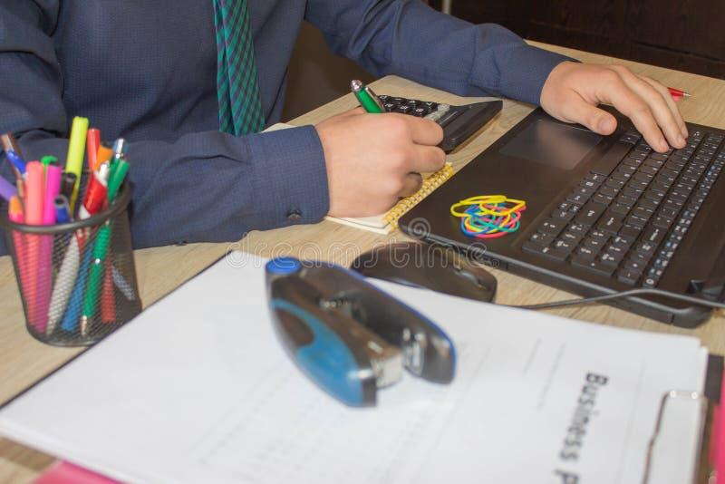 Hombre de negocios corporativo que trabaja en el escritorio de oficina, él está utilizando una calculadora Sirva hacer su contabi imágenes de archivo libres de regalías