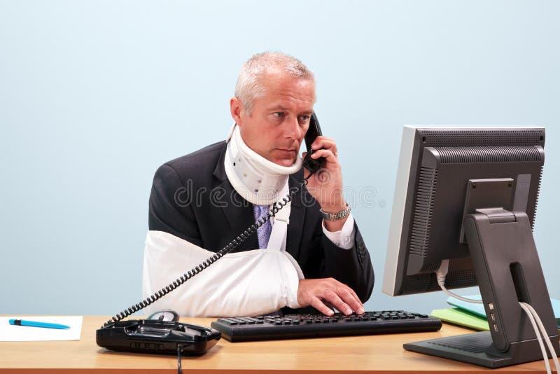 Hombre de negocios dañado en su escritorio en el teléfono fotos de archivo