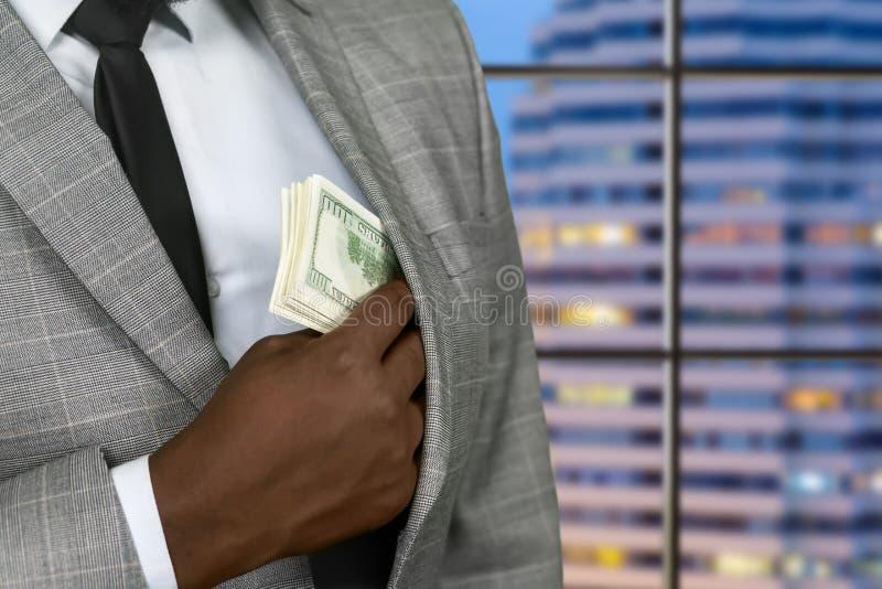 Hombre de negocios Darkskinned que oculta dólares americanos fotografía de archivo