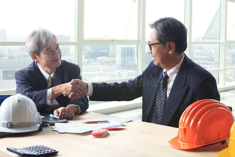 Hombre de negocios de construcción de dos ingenieros que sacude la mano después de projec fotografía de archivo libre de regalías
