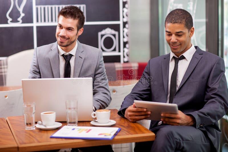 Hombre de negocios de dos jóvenes en el descanso para tomar café foto de archivo