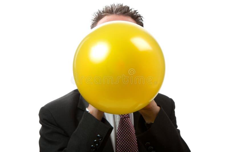 Hombre de negocios de la cara que hace saltar un globo imagen de archivo