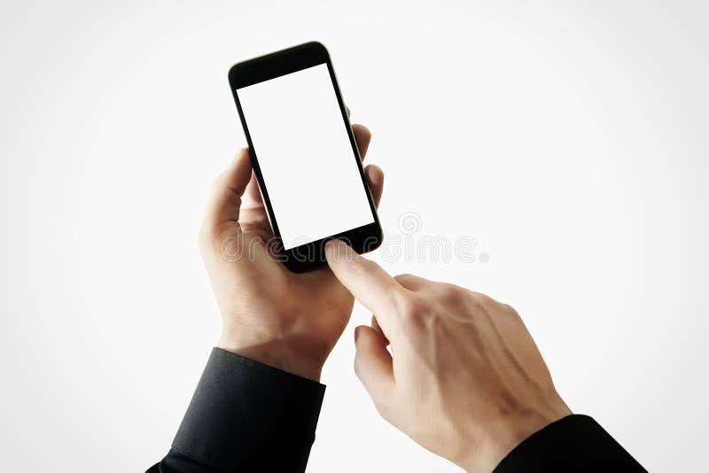 Hombre de negocios de la foto que lleva a cabo la mano moderna del smartphone, pantalla en blanco conmovedora Fondo blanco, vacío imagen de archivo